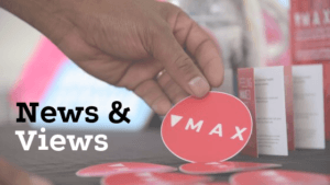 news and views of MAX Ottawa. Man picking up MAX sticker with MAX brochures in the background